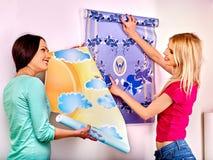 Las mujeres pegan el papel pintado en casa Imagen de archivo