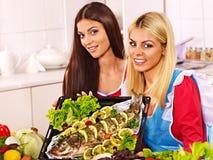 Las mujeres preparan pescados en horno. Imagenes de archivo