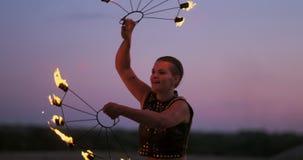 Las mujeres profesionales de los bailarines hacen una demostración del fuego y un funcionamiento pirotécnica en el festival con l metrajes