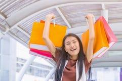 Las mujeres que disfrutaban de hacer compras, mujer sonriente aumentaron para arriba color Fotografía de archivo