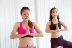 Las mujeres que ejercitan yoga presentan en clase del gimnasio de la aptitud Imagen de archivo