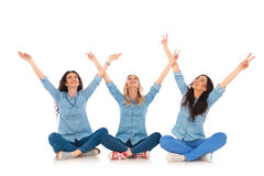 Las mujeres que hacen la victoria firman mientras que se sientan y miran para arriba Imágenes de archivo libres de regalías