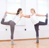 Las mujeres que hacen yoga ejercitan en la gimnasia Imagenes de archivo