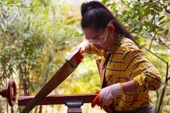 Las mujeres que la colocación es arte que trabaja la madera cortada en un banco de trabajo con las sierras circulares las herrami fotos de archivo libres de regalías
