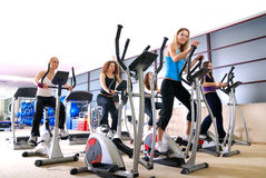 Las mujeres que se resuelven en el giro bikes en la gimnasia Imágenes de archivo libres de regalías