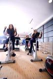 Las mujeres que se resuelven en el giro bikes en la gimnasia Foto de archivo