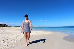 Las mujeres que tardan una mañana dan un paseo abajo de la playa del puerto Foto de archivo