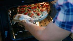 Las mujeres quitan la quiche francesa recientemente cocida del horno metrajes