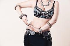 Las mujeres realizan danza de vientre en vestido étnico en fondo beige fotos de archivo