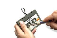 Las mujeres rebobinan un casete del acuerdo del vintage de la cinta de casete en el fondo blanco, cierre encima del sistema de vi fotografía de archivo libre de regalías