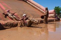 Las mujeres resbalan dentro del funcionamiento de Muddy Pit At Dirty Girl Mud Fotos de archivo