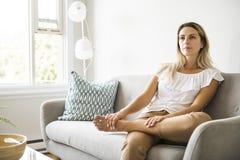 Las mujeres rubias agradables se sientan en el sofá en casa foto de archivo