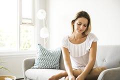 Las mujeres rubias agradables se sientan en el sofá en casa fotos de archivo