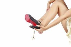 Las mujeres sacan los zapatos del alto talón. foto de archivo