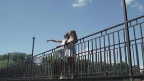 Las mujeres se están colocando en el puente Cielo azul en fondo almacen de video