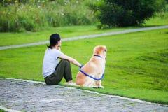 Las mujeres se están sentando con su perro en un parque fotografía de archivo
