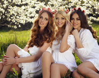 Las mujeres sensuales magníficas con el pelo lujoso en el vestido elegante que presenta en flor cultivan un huerto Imagenes de archivo