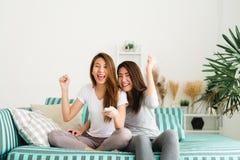 Las mujeres sonrientes jovenes de los amigos en casa que se sientan en el sofá y la TV de observación, ella está sosteniendo un t Fotografía de archivo libre de regalías