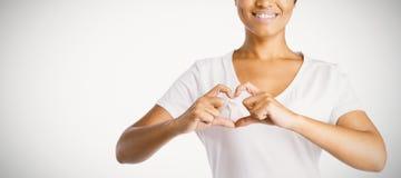 Las mujeres sonrientes que hacen el corazón forman con sus fingeres alrededor de cinta rosada fotos de archivo