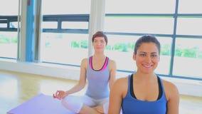 Las mujeres sonrientes que se sientan en las esteras de la yoga en la yoga clasifican metrajes
