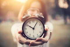 Las mujeres sostienen el reloj del vintage en su mano para mostrar épocas Fotos de archivo