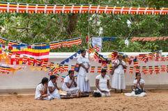 Las mujeres srilanquesas ruegan en el templo budista Imagenes de archivo