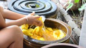 Las mujeres tailandesas atan el batik que teñe color natural amarillo almacen de metraje de vídeo
