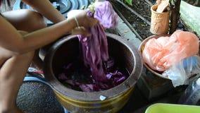 Las mujeres tailandesas atan el batik que teñe color natural rojo y rosado almacen de metraje de vídeo