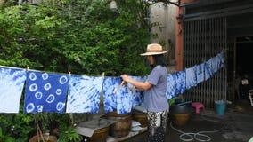 Las mujeres tailandesas atan la ropa seca de teñido del proceso de la ejecución del color del añil del batik en el sol almacen de metraje de vídeo
