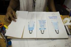 Las mujeres tailandesas del diseñador que dibujan y la moda del modelo del diseño en el papel para hacen al tablero del humor Fotos de archivo libres de regalías
