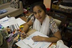 Las mujeres tailandesas del diseñador que dibujan y la moda del modelo del diseño en el papel para hacen al tablero del humor Foto de archivo libre de regalías