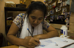 Las mujeres tailandesas del diseñador que dibujan y la moda del modelo del diseño en el papel para hacen al tablero del humor Imágenes de archivo libres de regalías