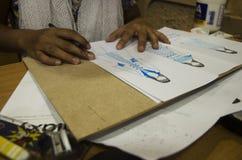 Las mujeres tailandesas del diseñador que dibujan y la moda del modelo del diseño en el papel para hacen al tablero del humor Imagen de archivo