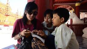 Las mujeres tailandesas enseñan los niños burmese al libro de lectura en la pagoda de Shwezigon almacen de video