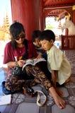 Las mujeres tailandesas enseñan los niños burmese al libro de lectura en la pagoda de Shwezigon fotos de archivo