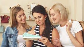 Las mujeres ven el zapato costoso en zapatería imagenes de archivo