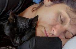 Las mujeres y el gato duermen juntos en cama Fotografía de archivo libre de regalías