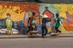 Las mujeres y el vendedor ambulante pasan delante de la pared del mosaico de la UNESCO. Fotografía de archivo libre de regalías