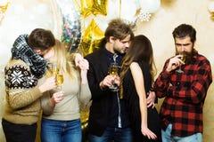 Las mujeres y los hombres disfrutan de la celebración del partido Los amigos celebran la Navidad o el Año Nuevo Champán de la beb Foto de archivo libre de regalías