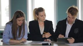 Las mujeres y un hombre que se sienta en fila en una tabla y conducen una reunión de negocios almacen de video