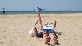 Las mujeres y un ni?o est?n mintiendo en la arena contra la perspectiva del mar Una madre y un niño pequeño están jugando un avió almacen de metraje de vídeo