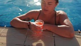 Las nadadas de la mujer al borde de la piscina, toman el jugo fresco, lo beben y nadan lejos, día soleado en la piscina metrajes