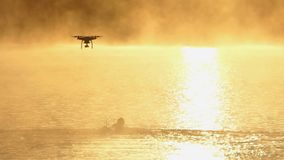 Las nadadas del hombre joven se arrastran en un lago en la puesta del sol en el slo-MES El abejón ha terminado almacen de metraje de vídeo