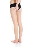 Las nalgas y las piernas hermosas de la mujer flexible y lisa. Imagen de archivo