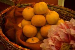 Las naranjas adornaron en una cesta con una flor fotografía de archivo