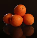 Las naranjas dan fruto contra el fondo del marrón oscuro para el texto Fotos de archivo libres de regalías