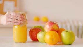 Las naranjas de las manzanas llenan el detox del smoothie de la botella de la mujer metrajes