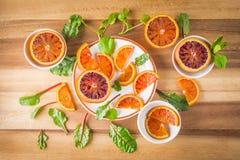 Las naranjas de sangre en las placas blancas con la ensalada se van imagen de archivo