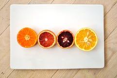 Las naranjas de sangre rojas de rubíes, las naranjas navel, y las clementinas cortaron por la mitad imagen de archivo