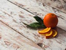 Las naranjas frescas dan fruto con las hojas verdes en la tabla de madera blanca Espacio del texto Foto de archivo libre de regalías